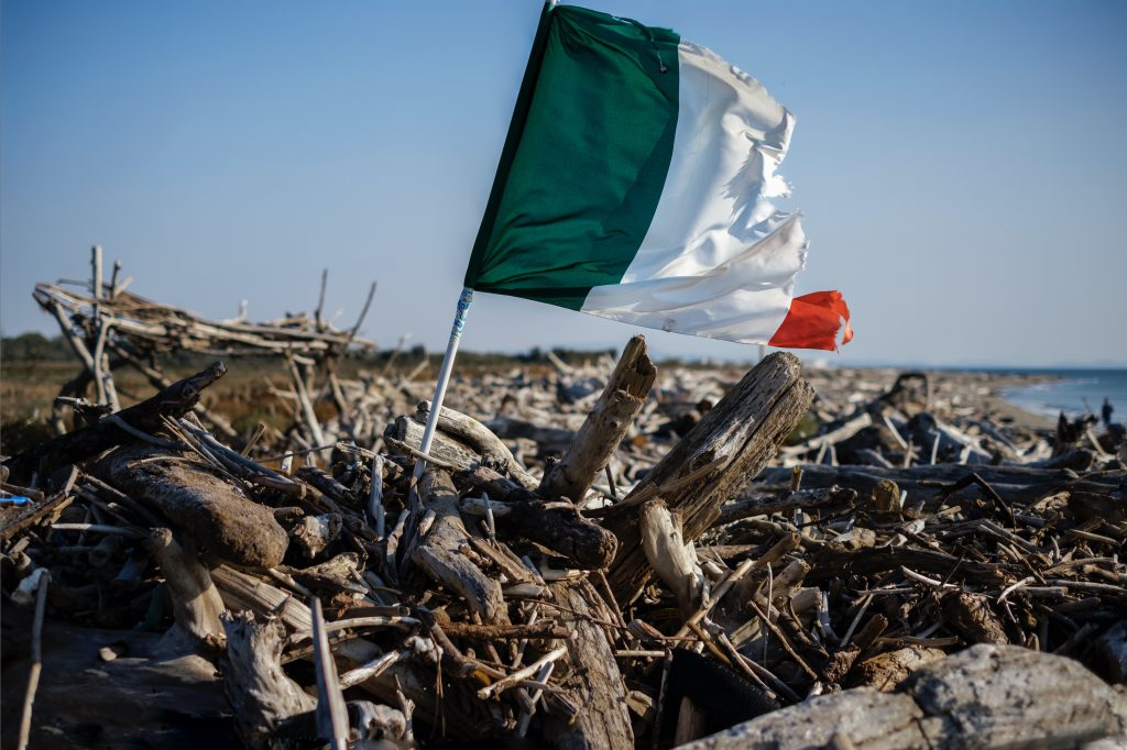 Bandiera italiana che sventola su tronchi abbandonati, Castelvolturno